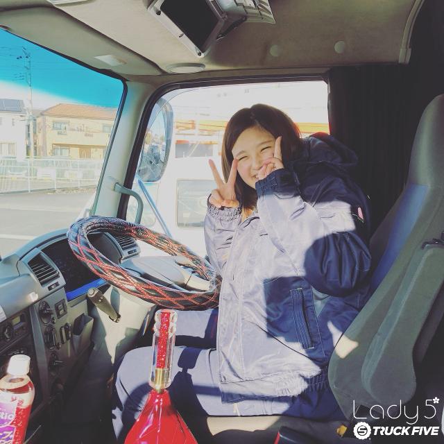 トラック内ポーズしている女性ドライバー